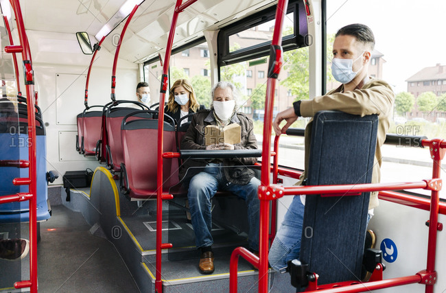 Passengers wearing protective masks in public bus- Spain