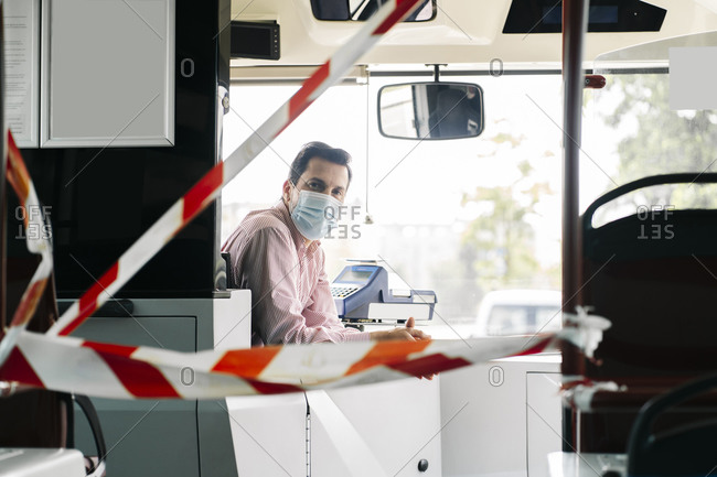 Portrait of mature bus driver wearing protective mask behind caution tape in public bus- Spain