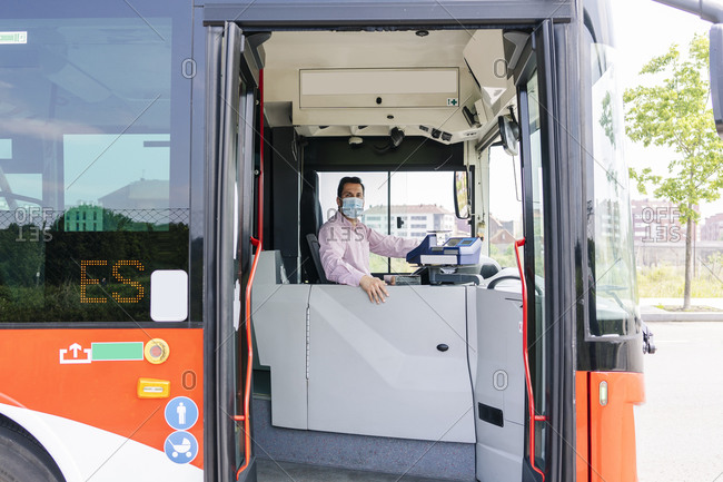 Mature bus driver wearing protective mask waiting at bus station- Spain