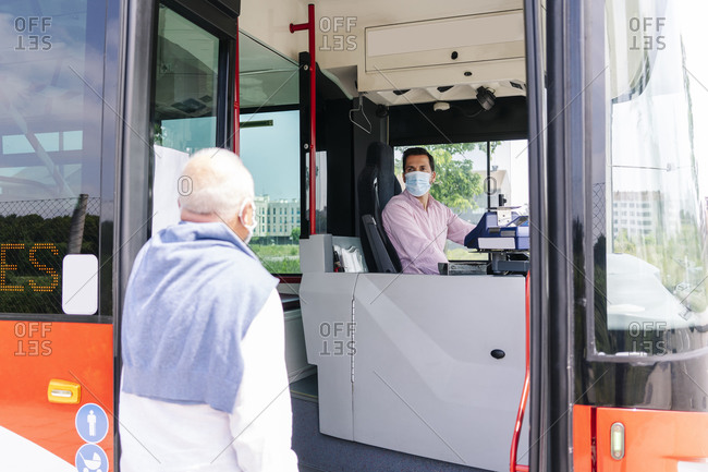 Bus driver wearing protective mask talking to passenger at bus stop- Spain