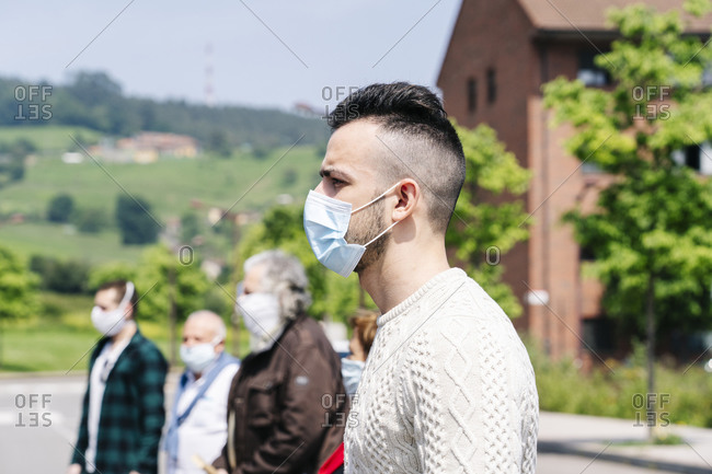 Profile of young man wearing protective mask waiting with other passengers at bus stop- Spain