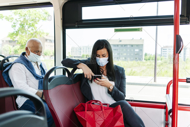 Businesswoman wearing protective mask sitting in public bus using cell phone- Spain