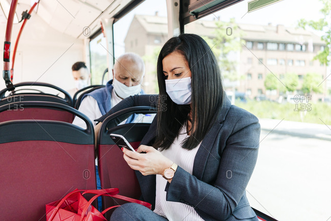 Businesswoman wearing protective mask in public bus looking at cell phone- Spain