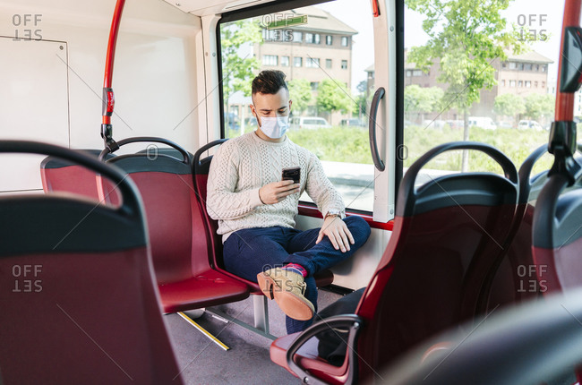 Young man wearing protective mask sitting in public bus looking at cell phone- Spain