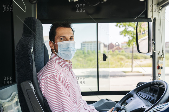 Portrait of mature bus driver wearing protective mask- Spain