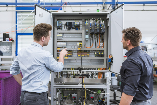 Two technicians working on circuit in factory
