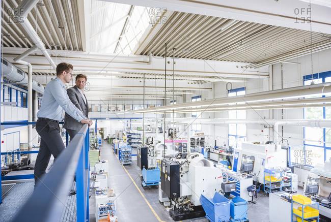 Two businessmen talking on upper floor in a factory