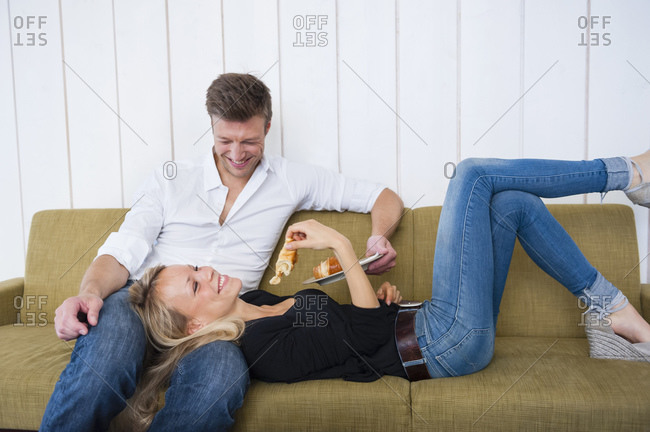Smiling woman eating croissant while lying on boyfriend's lap at home