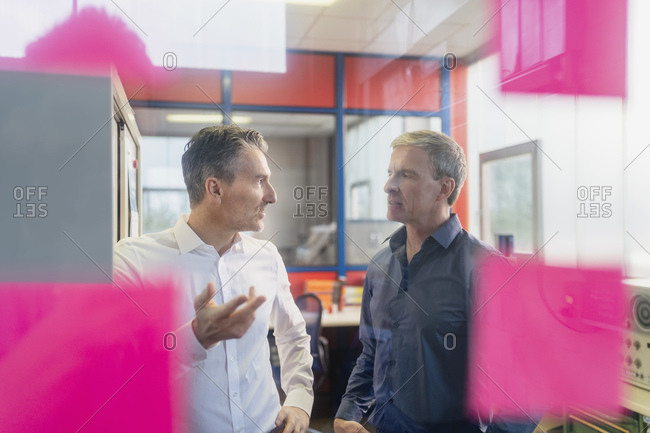 Confident male business partners planning strategy while standing in office during meeting