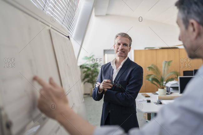 Confident mature businessman looking while listening to male colleague explaining strategy over whiteboard at office during meeting