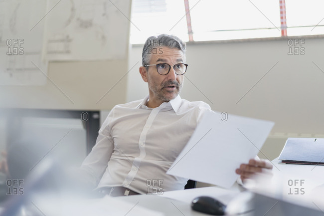 Confident businessman looking away with raised eyebrows while sitting with document at desk in office