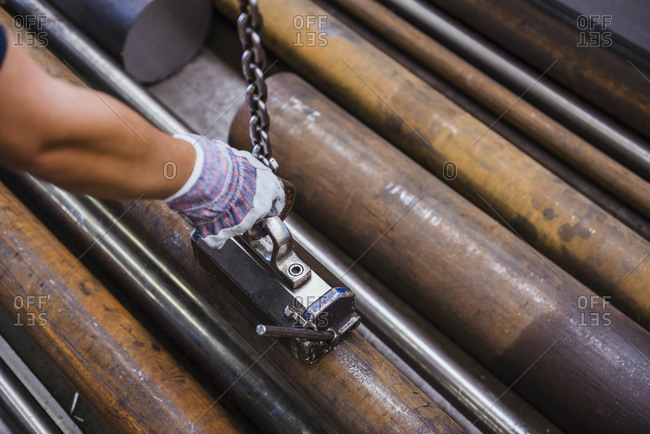 Close-up of man working with metal bars in a factory