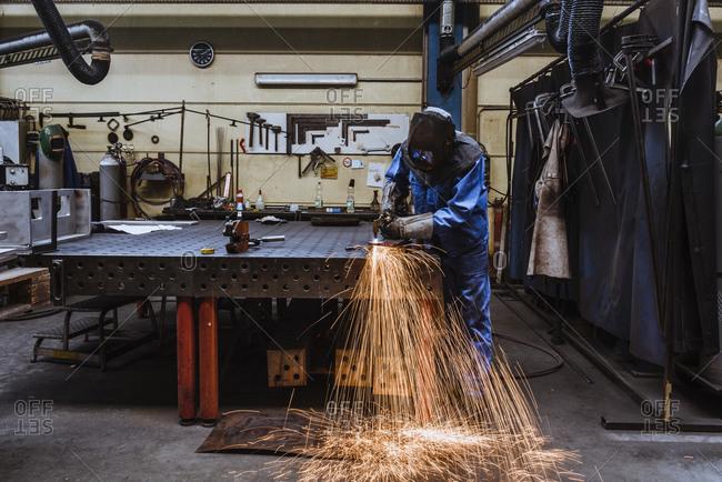 Welder welding metal in a factory
