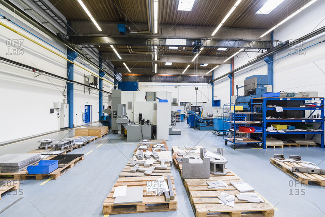 Empty factory shop floor with pallets and supplies