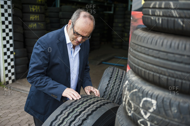 Senior male owner checking rubber tire at store