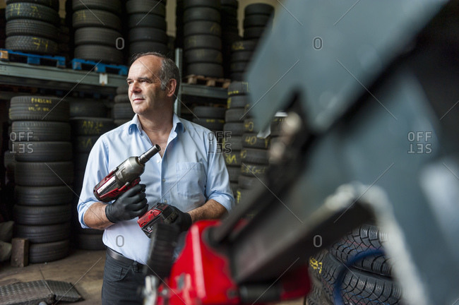 Senior entrepreneur holding impact wrench while looking away at tire store