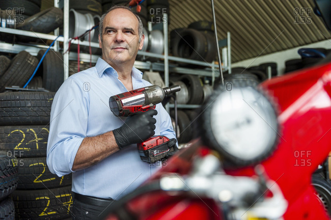 Confident senior businessman holding impact wrench while looking away at tire store
