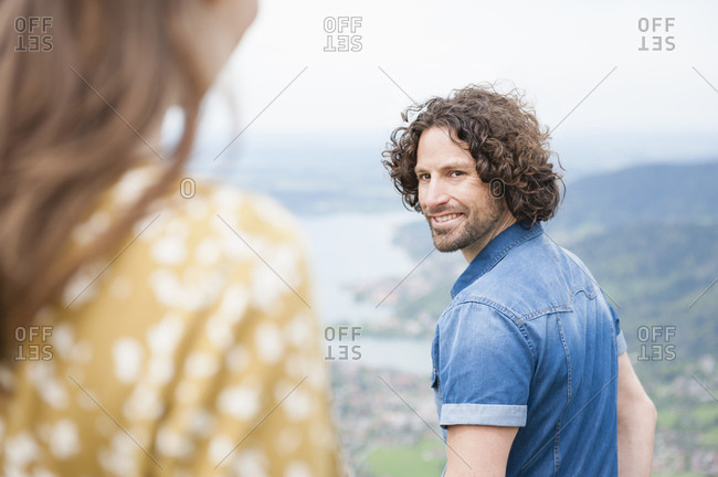 Smiling handsome man looking back at woman