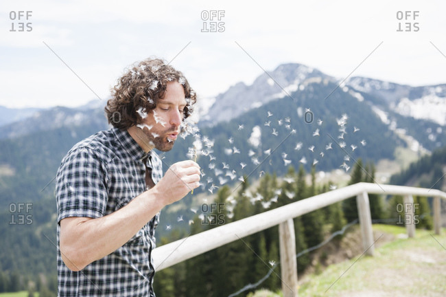 Handsome mid adult man blowing on dandelion seeds while standing against mountains on sunny day