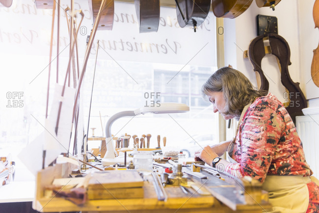 Female violin maker at work in her workshop