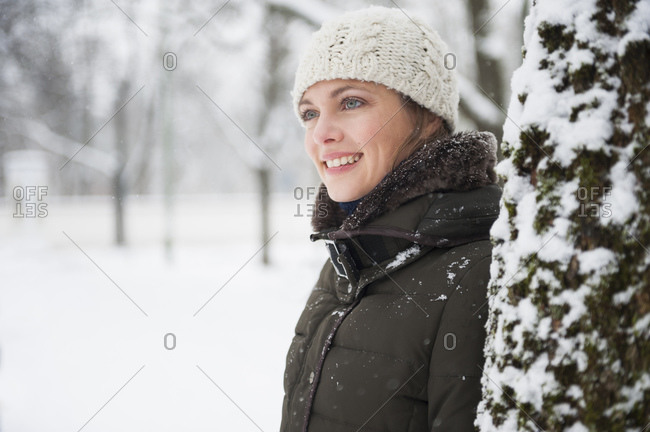 Portrait of smiling woman leaning at tree trunk in winter
