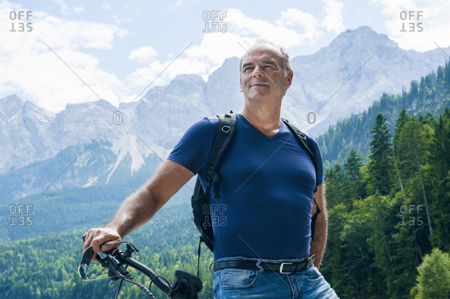 Senior man posing with e-bike on trail