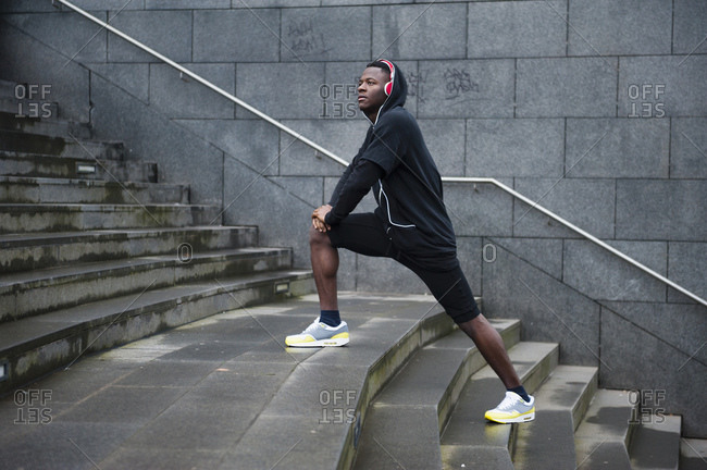 Young jogger stretching his leg in the city