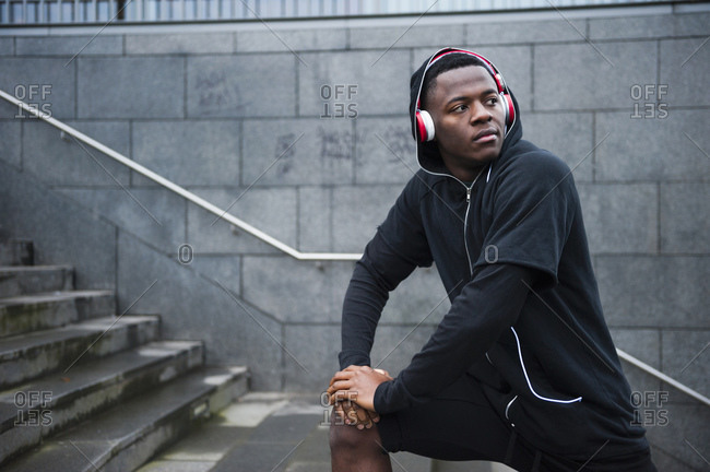 Portrait of young jogger with red headphones in the city