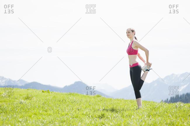 Female jogger stretching her leg- Wallberg- Bavaria- Germany