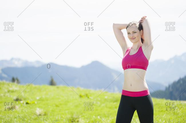 Female jogger stretching her arm- Wallberg- Bavaria- Germany