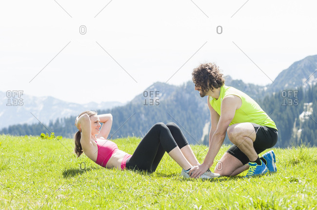 Couple during sit-ups on meadow- Wallberg- Bavaria- Germany