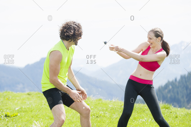 Female jogger squirting water to man- Wallberg- Bavaria- Germany
