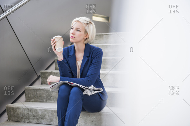 Portrait of blond businesswoman with coffee to go and newspaper sitting on stairs