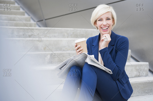 Portrait of blond laughing businesswoman with coffee to go and newspaper sitting on stairs