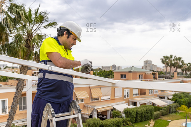 Mature male technician installing solar panel on roof while standing against sky