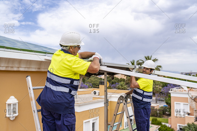 Male coworkers installing solar panels on house roof while standing over ladders against cloudy sky