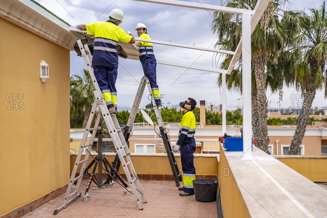 Man looking at coworkers installing solar panels on roof while standing in balcony