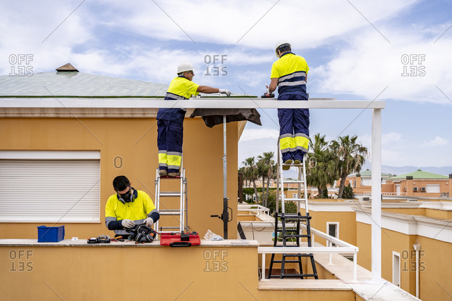 Male technicians installing solar panels on house roof against cloudy sky