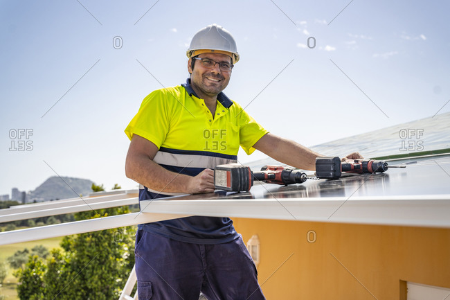 Portrait of smiling mature technician installing solar panel on house roof against sky
