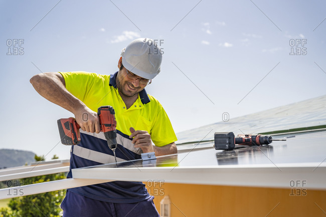 Smiling mature technician installing solar panel with drill on house roof against sky