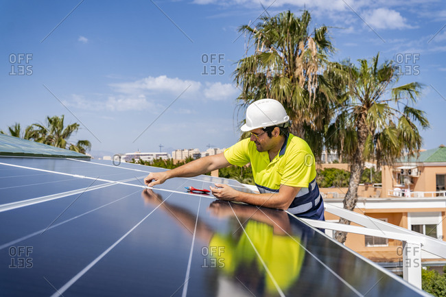 Mature technician installing solar panel on house roof against sky during sunny day