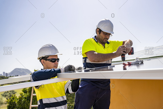 Male technicians installing solar panels on house roof against sky during sunny day