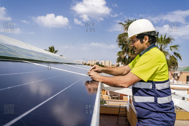 Mature technician installing solar panel on house roof against sky