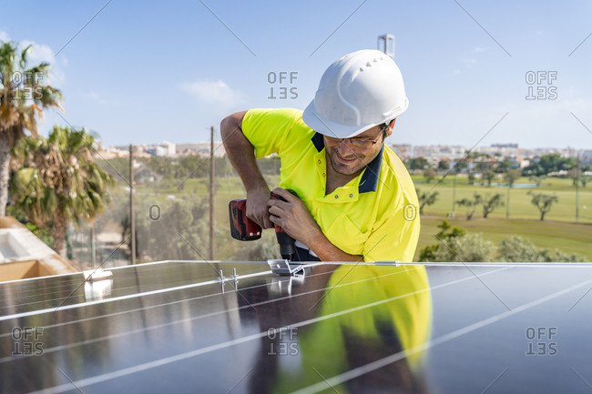 Male technician installing solar panel with drill on house roof against sky during sunny day