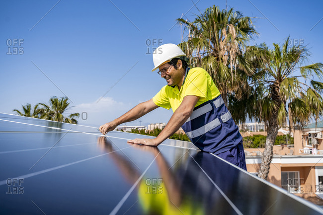 Smiling mature technician installing solar panel on house roof against blue sky