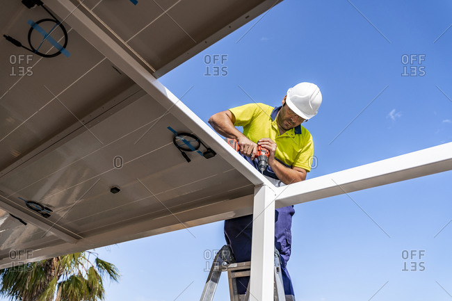 Mature technician installing solar panel on house roof against blue sky