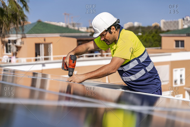 Mature technician installing solar panel with drill on house roof during sunny day