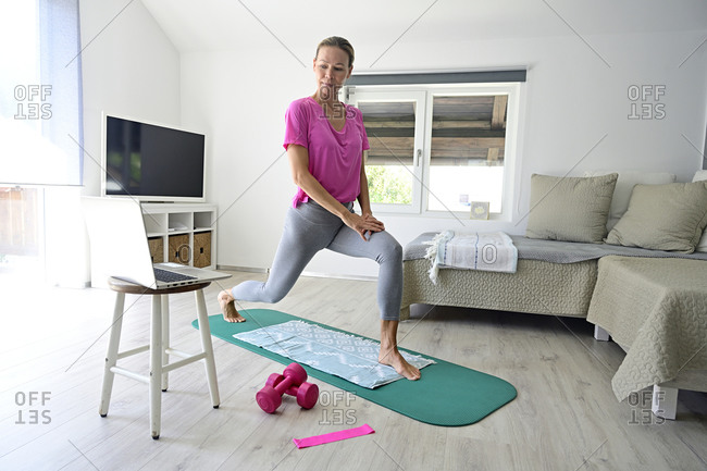 Mature woman with laptop practicing yoga on gym mat in living room