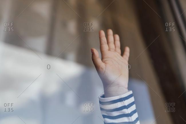 Little girl's hand behind windowpane