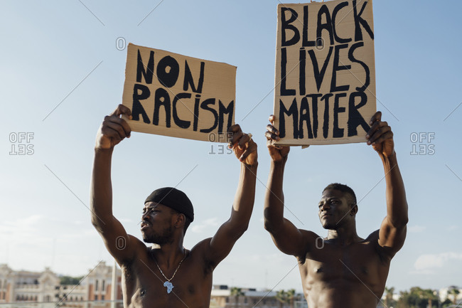 Two men holding Black Lives Matter and anti racism signs in the street